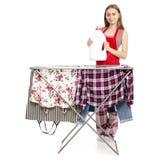 Donna in stendipanni dei vestiti del grembiule con la bottiglia di plastica dei vestiti puliti per il detersivo di lavanderia liq fotografia stock libera da diritti
