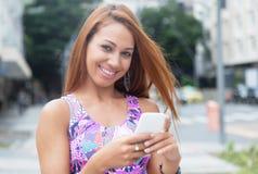 Donna straordinaria con il messaggio di battitura a macchina dei capelli rossi al telefono Immagine Stock Libera da Diritti