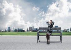 Donna stressante che si siede sul banco di legno immagine stock
