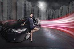 Donna stupefacente di bellezza che posa accanto alla sua automobile fotografia stock