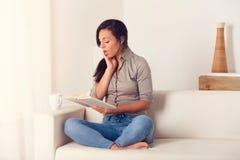 Donna stupita che legge un libro sullo strato a casa Immagini Stock Libere da Diritti