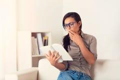 Donna stupita che legge un libro sullo strato a casa Fotografie Stock Libere da Diritti