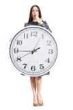 Donna stupita che tiene grande orologio Immagini Stock
