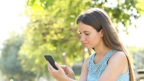 Donna stupita che trova il contenuto impressionante del telefono video d archivio