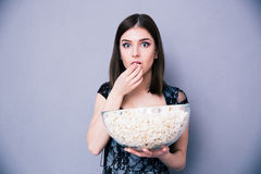 Donna stupita giovani che mangia popcorn Fotografie Stock