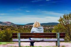 Donna su un banco, esaminante un paesaggio mediterraneo immagine stock libera da diritti