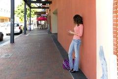 Donna su un marciapiede facendo uso di un cellulare Immagini Stock Libere da Diritti
