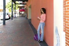 Donna su un marciapiede facendo uso di un cellulare Fotografie Stock