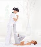 Donna su un massaggio tailandese su un fondo della stazione termale Fotografie Stock Libere da Diritti