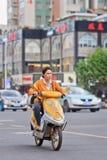 Donna su una e-bici gialla, Kunming, Cina Fotografia Stock