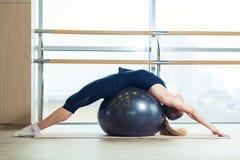Donna su una palla di forma fisica in palestra Immagini Stock