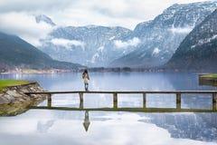 Donna su una piattaforma sopra un lago alpino Fotografia Stock