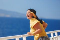 Donna su una vacanza di crociera stando sulla piattaforma della nave da crociera, forte vento che soffia i suoi capelli immagini stock libere da diritti