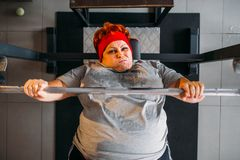 Donna sudata grassa, allenamento con il bilanciere in palestra Fotografia Stock