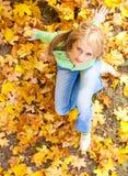 Donna sui fogli di autunno Immagini Stock Libere da Diritti