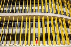 Donna sui precedenti gialli della costruzione Immagine Stock