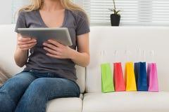 Donna sui sacchetti della spesa di Sofa With Digital Tablet And Fotografie Stock Libere da Diritti
