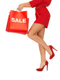 Donna sui tacchi alti che tengono i sacchetti della spesa Immagini Stock
