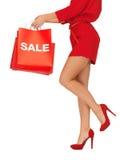 Donna sui tacchi alti che tengono i sacchetti della spesa Fotografia Stock