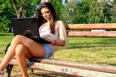 Donna sul banco con il taccuino fotografia stock libera da diritti