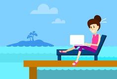 Donna sul lettino facendo uso dell'isola Banaba tropicale della spiaggia del computer portatile del lavoro a distanza del posto d Immagini Stock