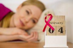 Donna sul letto, giorno del cancro al seno del mondo sul calendario Immagini Stock Libere da Diritti