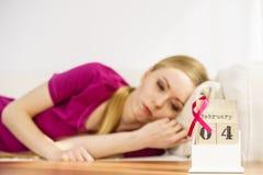 Donna sul letto, giorno del cancro al seno del mondo sul calendario Immagine Stock Libera da Diritti