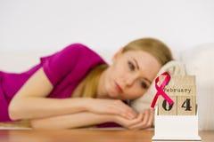 Donna sul letto, giorno del cancro al seno del mondo sul calendario Immagini Stock