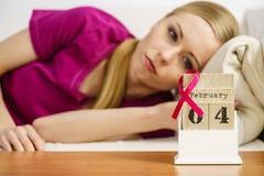 Donna sul letto, giorno del cancro al seno del mondo sul calendario Fotografie Stock Libere da Diritti