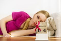 Donna sul letto, giorno del cancro al seno del mondo sul calendario Fotografie Stock