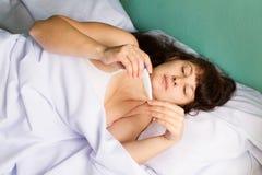 Donna sul letto la febbre alta Immagine Stock Libera da Diritti