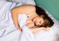 Donna sul letto la febbre alta Fotografie Stock Libere da Diritti