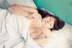 Donna sul letto la febbre alta Fotografia Stock Libera da Diritti