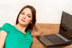 Donna sul pavimento con il computer portatile Fotografie Stock