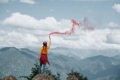 Donna sul picco di montagna con il chiarore rosso Concetto di ispirazione immagini stock libere da diritti