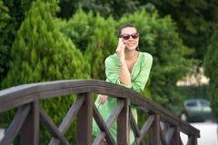 Donna sul ponte che parla sul telefono fotografie stock