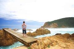 Donna sul ponticello vicino all'oceano fotografia stock libera da diritti