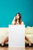 Donna sul sofà che tiene il bordo di presentazione vuota fotografie stock libere da diritti