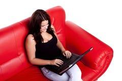 Donna sul sofà con il calcolatore. Fotografia Stock