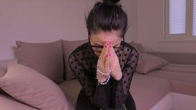 Donna sul sofà con pregare della croce e della bibbia archivi video