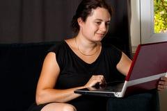 Donna sul sofà con un computer portatile Fotografia Stock