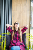 Donna sul suo lavoro, pendente lei indietro su una sedia con le mani alla suoi testa ed occhi chiusi, rmphasizing del pensiero de Fotografie Stock
