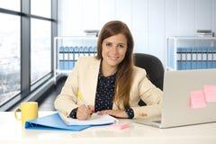 Donna sul suo 30s all'ufficio che lavora allo scrittorio del computer portatile che prende le note Immagini Stock Libere da Diritti