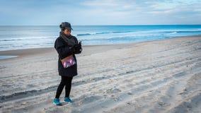 Donna sul telefono cellulare della tenuta della spiaggia con l'oceano dietro lei fotografia stock libera da diritti
