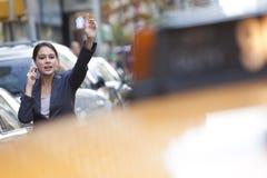 Donna sul telefono delle cellule che grandina una carrozza di tassì gialla Immagine Stock