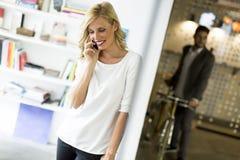 Donna sul telefono nell'ufficio fotografia stock