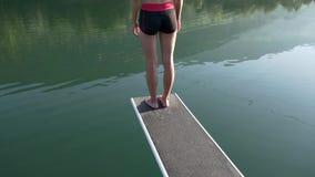 Donna sul trampolino che prepara tuffarsi un lago stock footage