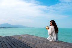 Donna sul vestito bianco che si siede al succo bevente della noce di cocco del terrazzo con il fondo del cielo blu e del mare con Fotografie Stock Libere da Diritti
