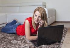 Donna sul vicino mobile il suo computer portatile Immagine Stock Libera da Diritti