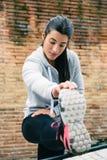 Donna sull'allenamento urbano della via che allunga le gambe Fotografia Stock